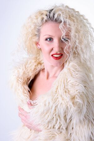 Curly blonde in a white fluffy fur coat Stock Photo - 8791120