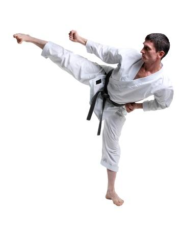 Karate. Man in a kimono hits foot on the white background Stock Photo