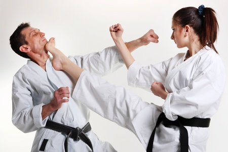 karate kick: Karate. Young girl and a men in a kimono with a white background. Battle sports capture