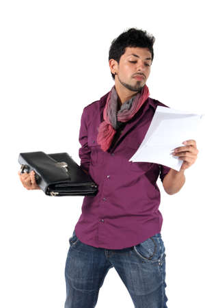 young businessman with a briefcase on the white background. A man reads a document photo