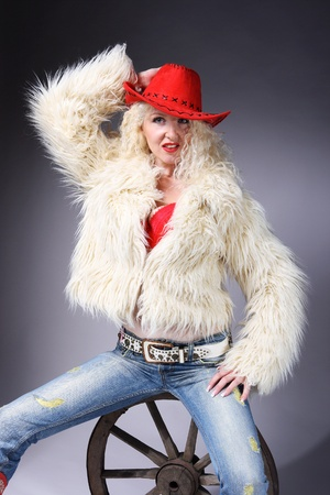 Curly blonde in a red hat and white fluffy fur coat. A girl sits on an old wooden wheel Stock Photo - 9230633