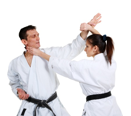 female kick: Karate. Young girl and a men in a kimono with a white background. Battle sports capture