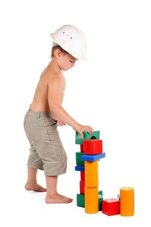 Little boy builds a house of toys on the white background photo