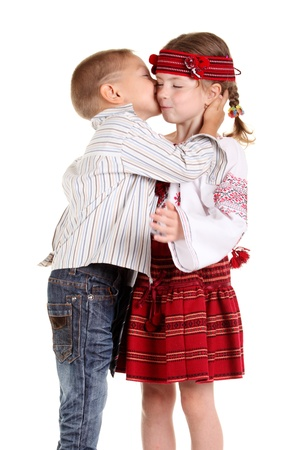 Little boy kissing a little girl on the white background