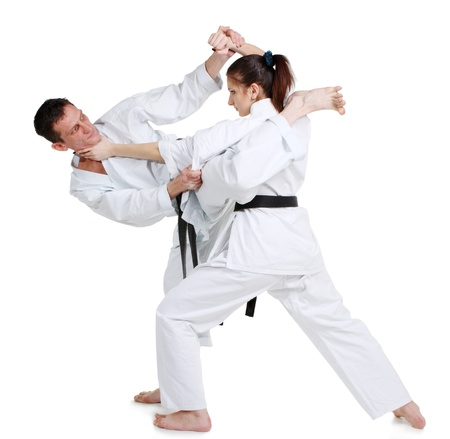 Karate. Young girl and a men in a kimono with a white background. Battle sports capture