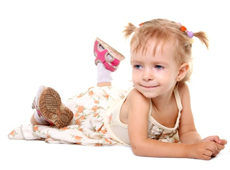 Little girl lying on her stomach on the white background photo