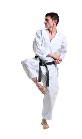 Karate. Man in a kimono with a white background photo