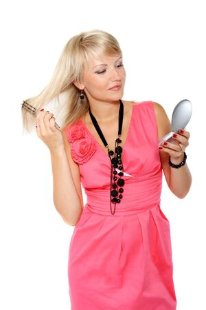 Beautiful young girl combing her hair before a mirror with a white background photo