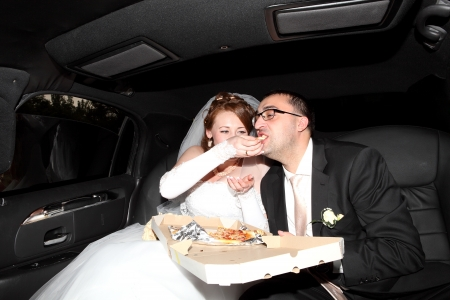 bride and groom eating pizza in the limousine photo