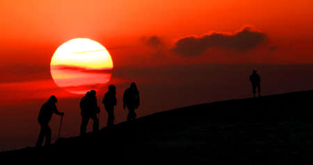 Group of tourists take to the mountains at sunset  Silhouette photo