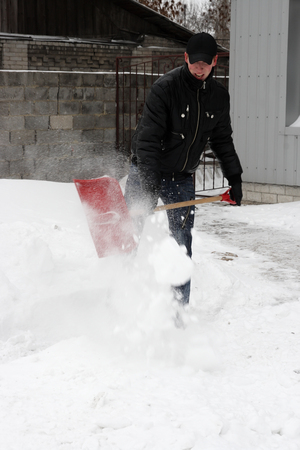 man shoveling snow in a snow storm  photo
