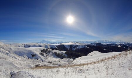 elbrus: Large halo around the sun on a winter day in mountains Elbrus. North Caucasus, Russia.