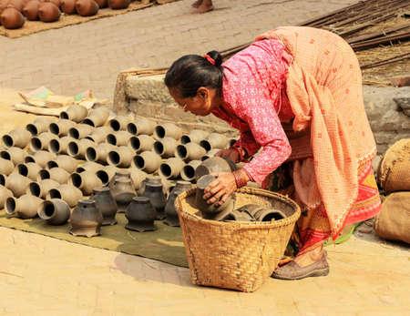 nepali: BHAKTAPUR, NEPAL, APRIL 03: Nepali woman dries the clay vases. Bhaktapur, Nepal on April 03, 2014 Editorial