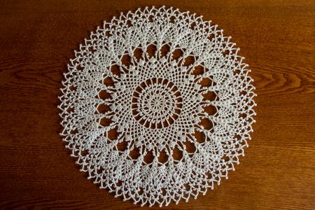 Round white crochet lace hanmdmade doily on wood