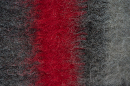 counterpane: Close-up of black handmade woollen felt blanket with red stripe