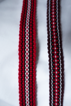 Two narrow woven tapes in with ethnic pattern in red, purple, black and white