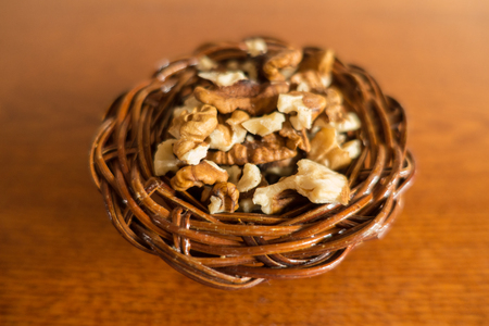 Walnut kernels in snall wicker basket on wood