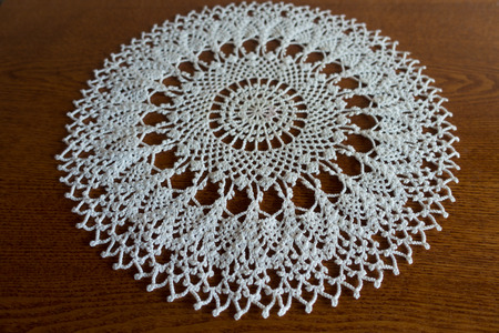 Round white handmade crochet lace doily on wooden table Stock Photo