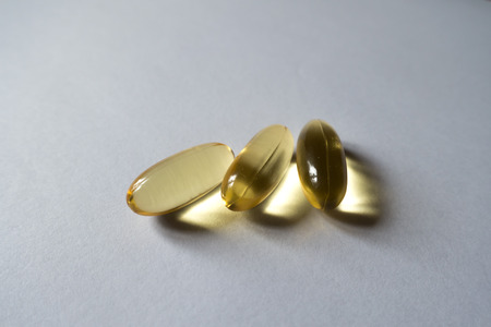 Three softgels of evening primrose oil on neutral background Stock Photo