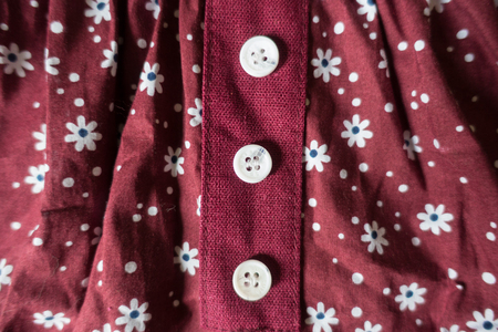 Three white buttons on maroon linen with floral print