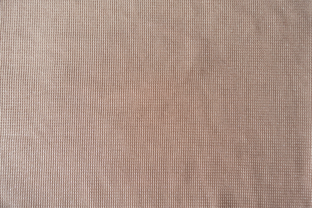 Texture of peach colored polyester fabric from above