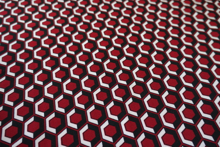 surface of fabric with geometric print in red black and white stock