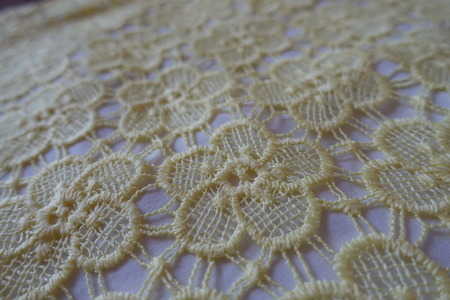 Pastel yellow lacy fabric with floral pattern