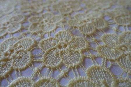 Perforated pale yellow thin crochet lacy fabric