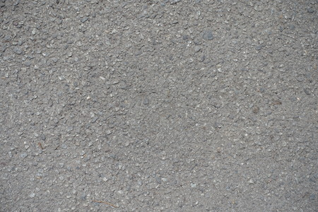 exasperate: Close up of grainy surface of dusty asphalt