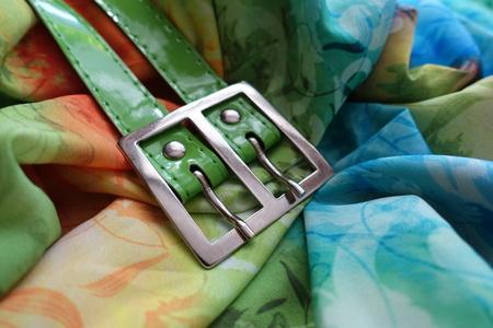 Buckle of green belt on draped colorful chiffon