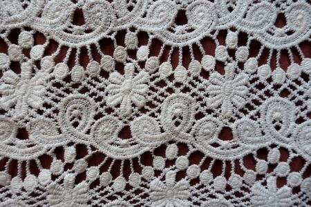 Macro of white lace with floral pattern from above