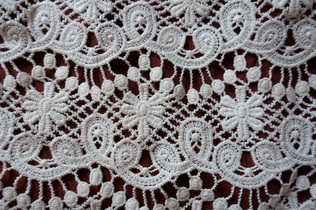 Perforated white lace with floral pattern from above