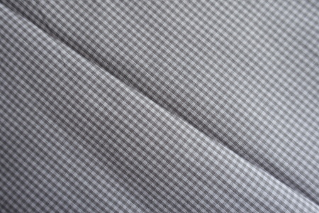 Diagonal crease on chequered grey cotton fabric