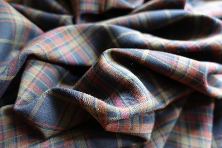 Folded thick plaid fabric in subdued colors Stock Photo