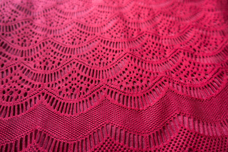 Curvilinear geometric pattern on red lacy fabric Imagens