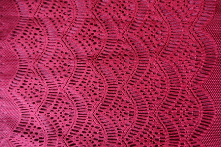 Top view of red lacy cotton fabric