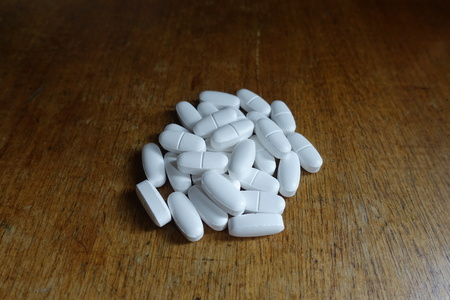 Batch of calcium citrate tablets on wooden table