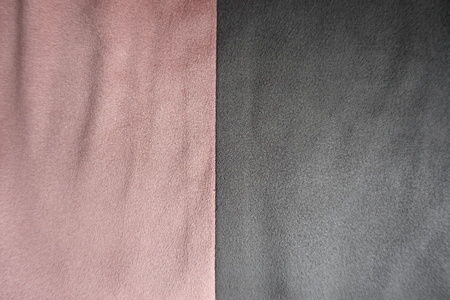 Pieces of pink and grey artificial suede sewn together vertically Stock Photo
