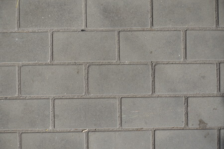 Dry grey concrete blocks pavement from above