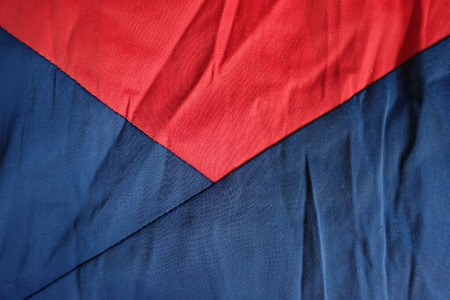 Parts of jammed navy and red cotton fabrics sewn together