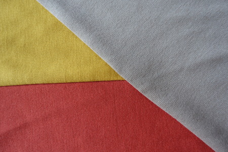 Parts of yellow, orange and beige fabrics sewn together Stock Photo