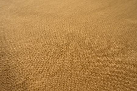 Closeup of simple amber yellow jersey fabric