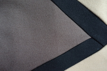 Triangular gusset of grey fabric sewn to beige and black fabric