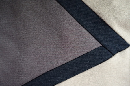 V-shaped black ribbons sewn to grey and beige fabric
