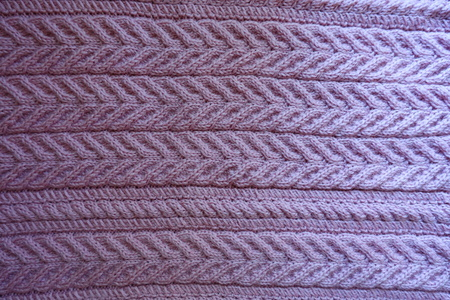 Top view of pink knitted fabric with relief stripes pattern