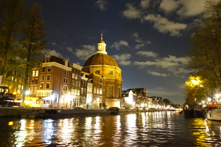 Ronde Lutherse Kerk next to Singel canal in Amsterdam at night Stock Photo