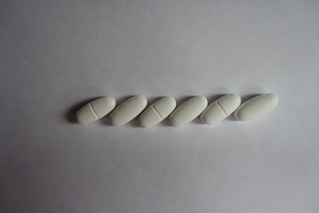 Horizontal line of white caplets of calcium citrate