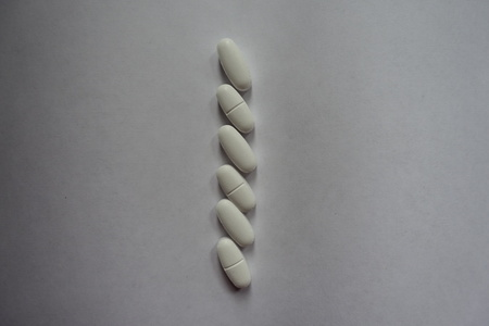 Vertical line of white caplets of calcium citrate 写真素材