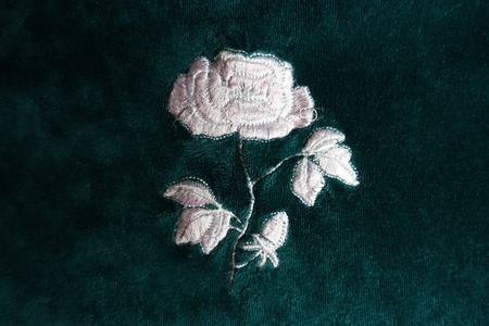 White flower embroidery on dark green velvet