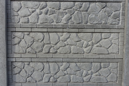 Composite concrete fence with stone like relief pattern